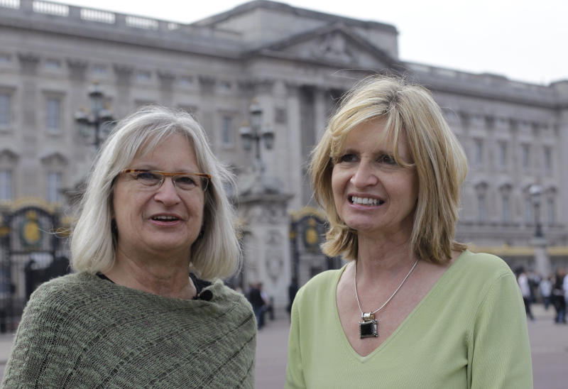 Sisters, Darla Herrnberger, right, and Sheree Troy from from Lincolnton, North Carolina, U.S.,   talk to The Associated Press, Tuesday, April 26, 2011, on The Mall with Buckingham Palace in the background, in London as the tourists scoped out the best spot to stand, ahead of the upcoming royal wedding of Britain's Prince William and Kate Middleton.  For hardcore fans of the British monarchy, sitting glued to the television with popcorn just doesn't cut it for an occasion like a royal wedding, being part of the crowds and soaking up the atmosphere is where to be, for  the happy occasion on April 29.  (AP Photo/Sang Tan)