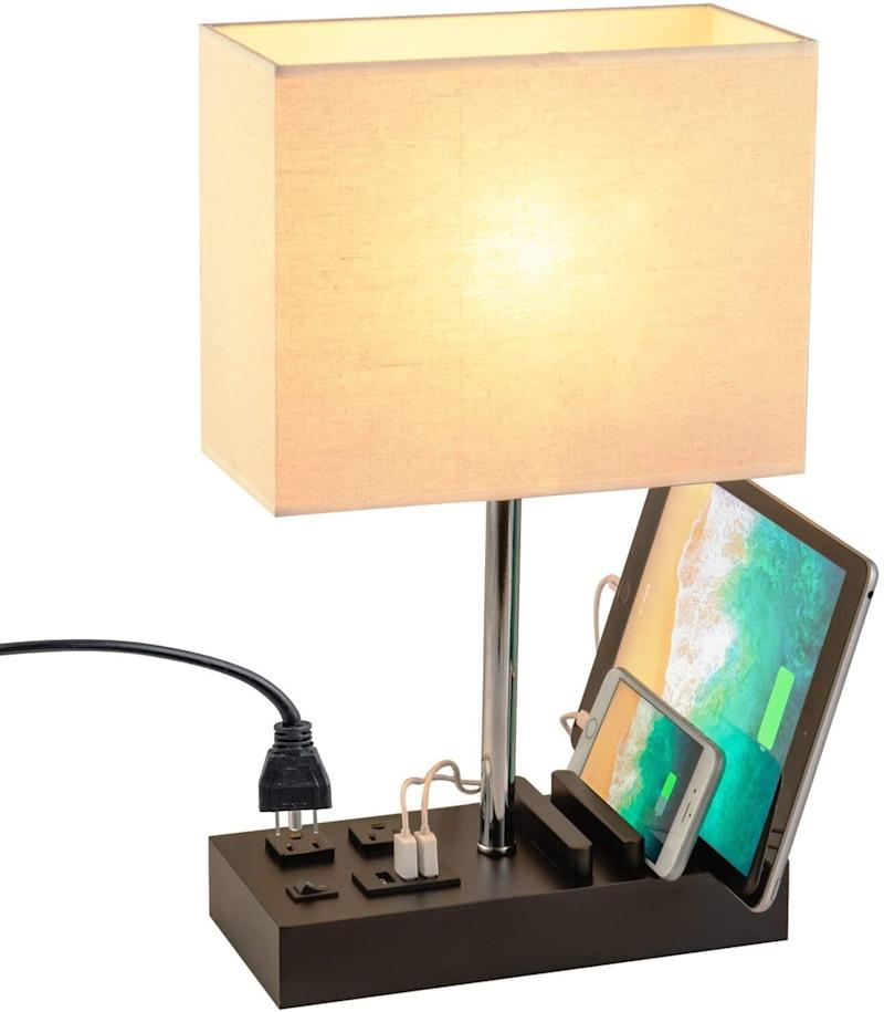 """When we say this desk lamp has everything, we mean it has<i> everything</i>&mdash;three USB charging ports, twoAC power outlets and holders for your phone and tablet. You'll still need to get an E26 bulb, though. <a href=""""https://amzn.to/3izyGG1"""" target=""""_blank"""" rel=""""noopener noreferrer"""">Find it for $42 at Amazon</a>."""
