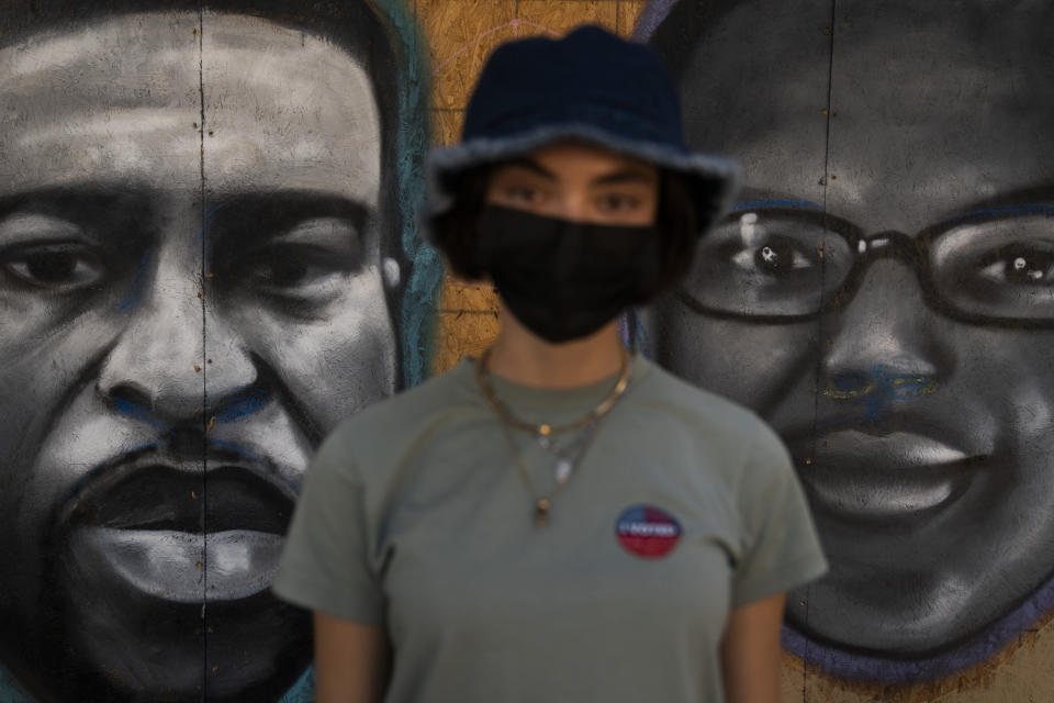 """Saoirse McNamara, a 20-year-old model, pauses for photos with her """"I Voted"""" sticker in front of a mural depicting George Floyd, left, and Elijah McClain Wednesday, Oct. 28, 2020, in Los Angeles. """"I've actually taken a photo of this mural because I think it's really beautiful. It holds true to a lot of what's happened this year. It's really important for people to walk by this and to be reminded of what has happened this year and how there's definitely extreme changes that we have to make within our society,"""" said McNamara who voted for Democratic presidential candidate former Vice President Joe Biden. (AP Photo/Jae C. Hong)"""