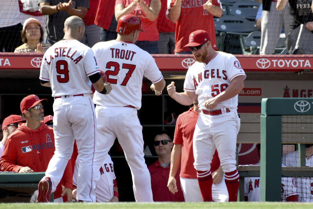 Los Angeles Angels' Mike Trout (27) is congratulated by Kole Calhoun, right, after hitting a two-run home run during the sixth inning against the Texas Rangers in a baseball game Sunday, April 7, 2019, in Anaheim, Calif. (AP Photo/Michael Owen Baker)