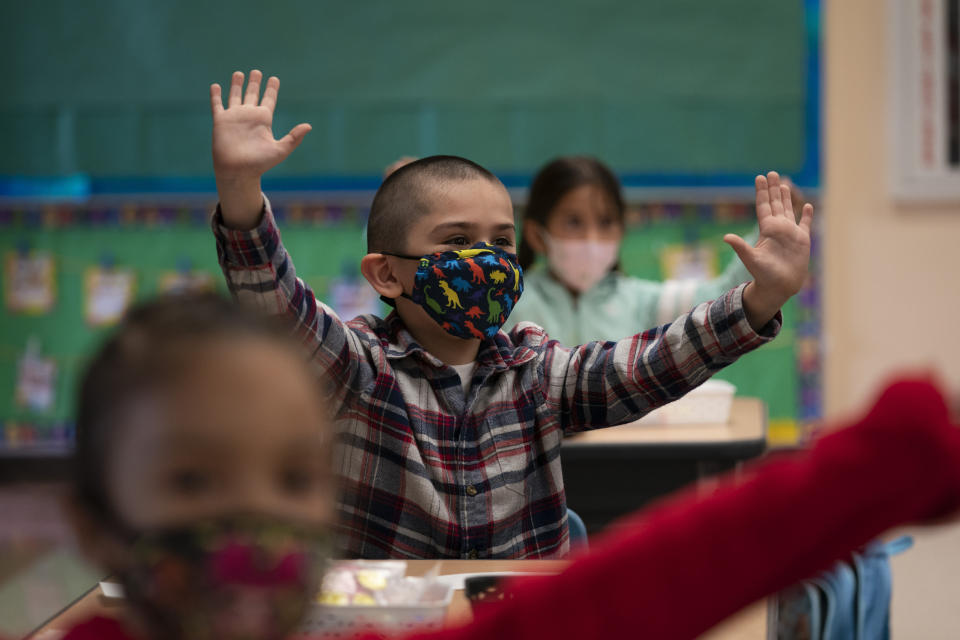 FILE — In this April 13, 2021 file photo Kindergarten students participate in a classroom activity on the first day of in-person learning at Maurice Sendak Elementary School in Los Angeles California schools have a few statewide requirements for how schools apply COVID rules for schools but leave most details up to the local districts, leading to a dizzying patchwork of approaches that parents and teachers say can be confusing and frustrating. (AP Photo/Jae C. Hong,File)