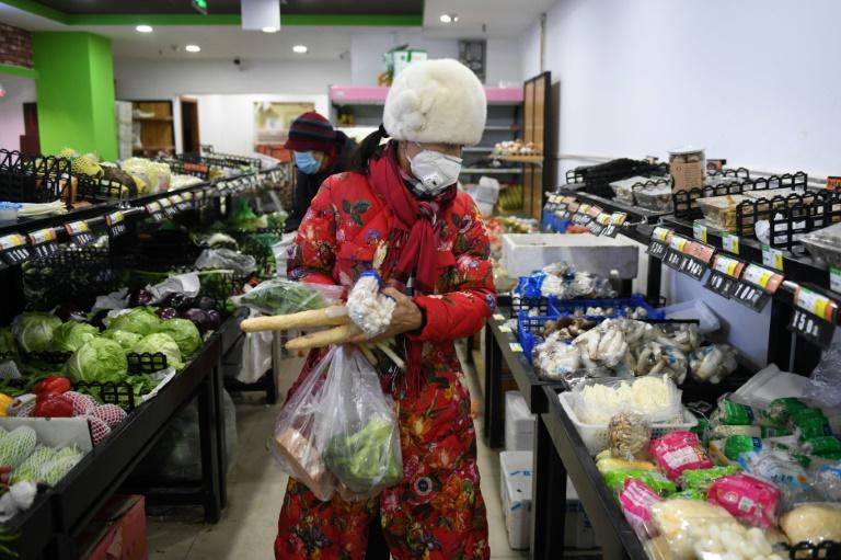 A woman shops at a market in Beijing, whose government requires people arriving from outside the city to self-quarantine for 14 days (AFP Photo/GREG BAKER)