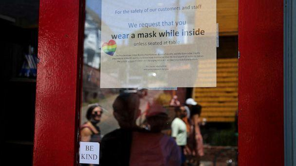 PHOTO: A sign at the Heaven Cafe encourages customers to wear masks until seated, in Provincetown, MA., on July 24, 2021. (Craig F. Walker/The Boston Globe via Getty Images)