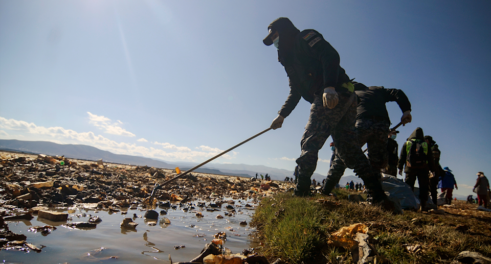 Men in shoots seen cleaning a lake.