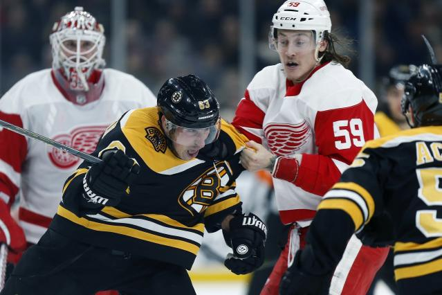 Detroit Red Wings' Tyler Bertuzzi (59) and Boston Bruins' Brad Marchand (63) fight during the second period of an NHL hockey game in Boston, Saturday, Dec. 1, 2018. (AP Photo/Michael Dwyer)