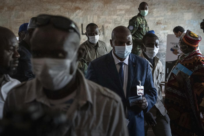 President Faustin-Archange Touadera, center, arrives to cast his vote at the Lycee Boganda polling station in the capital Bangui, Central African Republic, Sunday, Dec. 27, 2020. Touadera and his party said the vote will go ahead after government forces clashed with rebels in recent days and some opposition candidates pulled out of the race amid growing insecurity. (AP Photo)