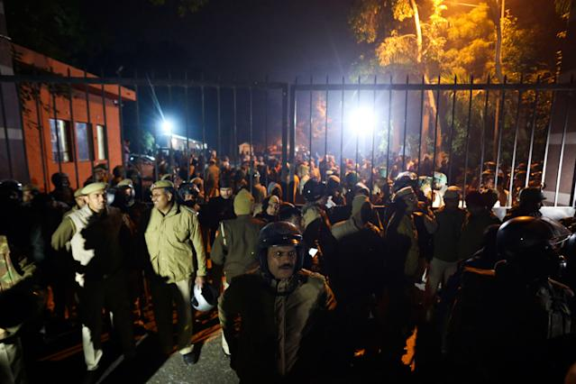 Police gather outside a gate of the Jawaharlal Nehru University (JNU) following alleged clashes between student groups in New Delhi on January 5, 2020. - At least 23 people were hurt at a prestigious Indian university on January 5 in what police said were clashes between rival student groups. The incident at JNU is the latest in a series of violent clashes and protests at different Indian universities in the last few weeks, with many student activists and opposition demonstrating against Modi government's controversial new citizenship law. (Photo by STR / AFP) (Photo by STR/AFP via Getty Images)