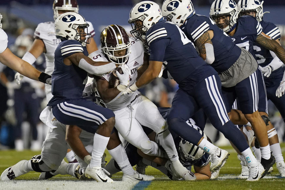 BYU's George Udo, left, and Pepe Tanuvasa, right, tackle Texas State running back Brock Sturges (5) in the first half during an NCAA college football game Saturday, Oct. 24, 2020, in Provo, Utah. (AP Photo/Rick Bowmer)