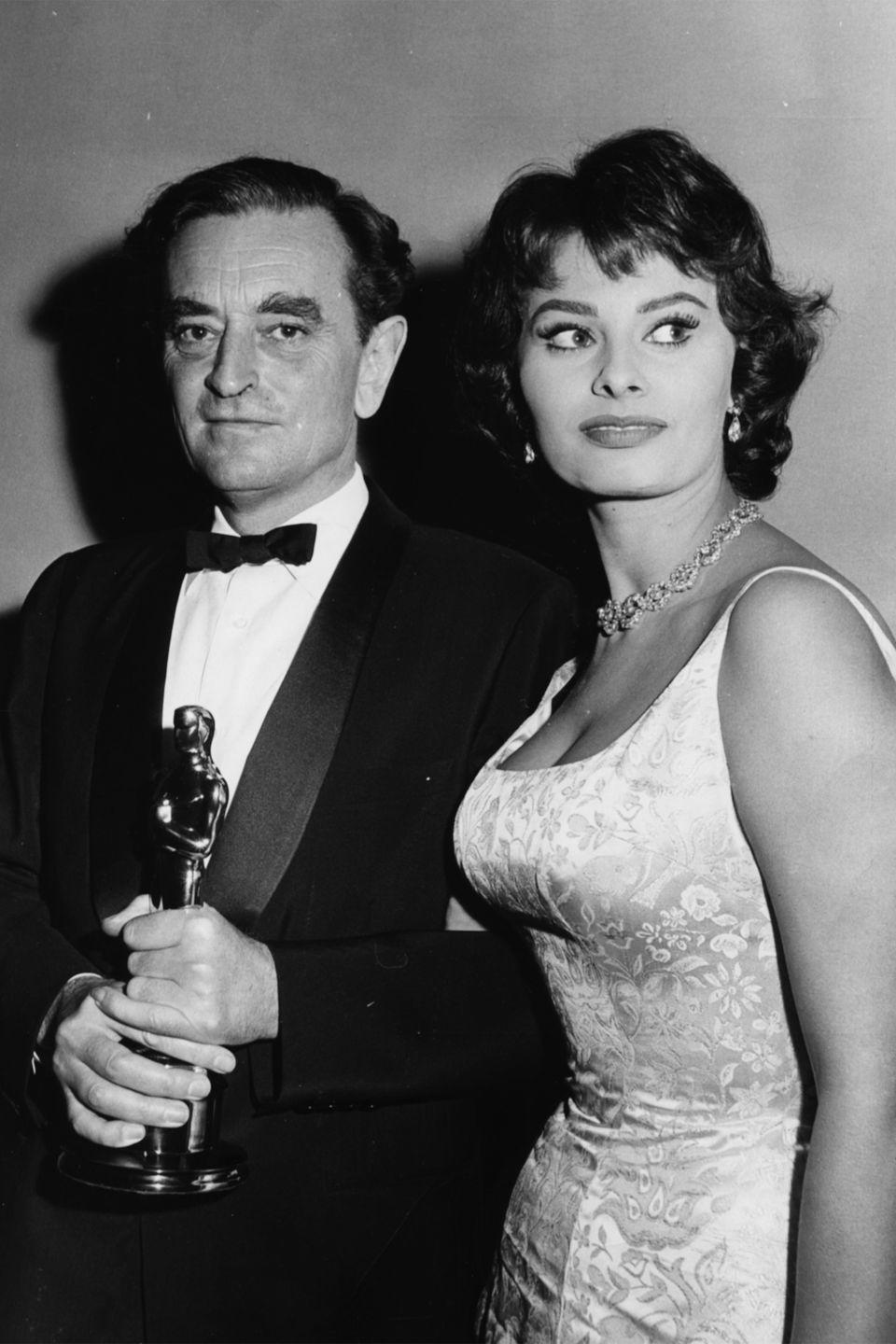 <p>Sophia Loren often dressed to show off her enviable curves, like this figure-hugging satin floral dress—diamond earrings and necklace complete the glamorous look. </p>
