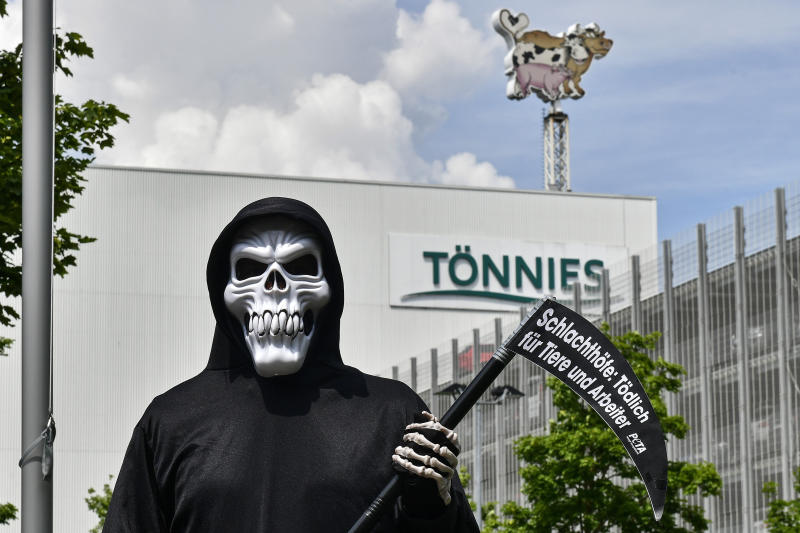 "A peta activist protests with a poster ""reading slaughterhouse - deadly for animals and workers"" in front of the Toennies meatpacking plant, Europe's biggest slaughterhouse, where the German Bundeswehr army helps to build up a test center for coronavirus in Rheda-Wiedenbrueck, Germany, Friday, June 19, 2020. Hundreds of new COVID-19 cases are linked to a large meatpacking plant, officials ordered the closure of the slaughterhouse, as well as isolation and tests for everyone else who had worked at the Toennies site — putting about 7,000 people under quarantine. (AP Photo/Martin Meissner)"