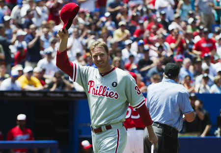 FILE PHOTO - Philadelphia Phillies pitcher Roy Halladay tips his hat to the crowd before his team plays the Toronto Blue Jays in their MLB Interleague baseball game in Toronto, July, 1, 2011. REUTERS/Mark Blinch