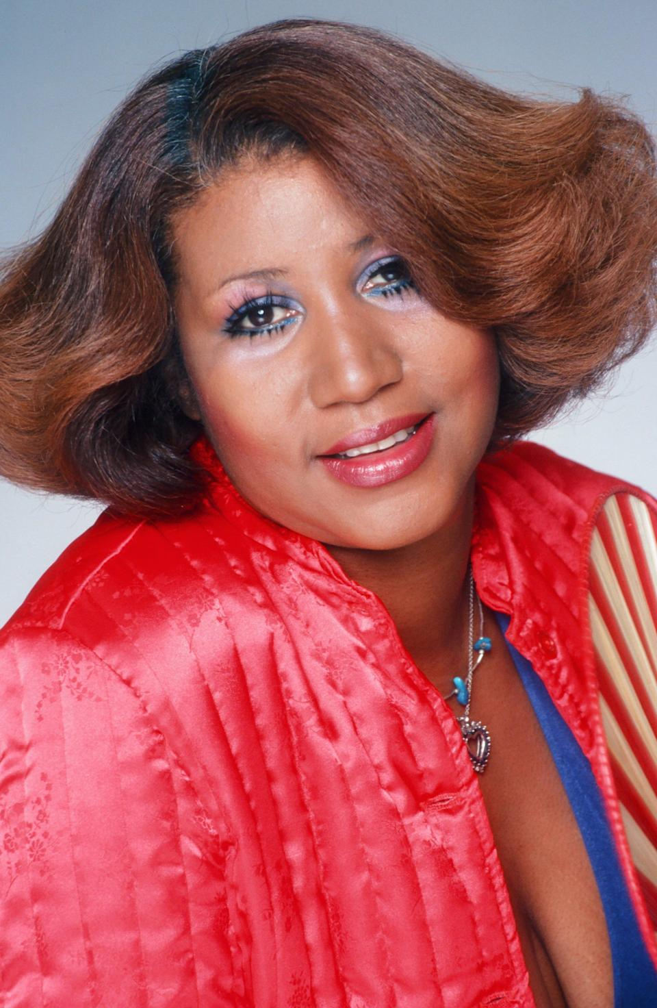 <p>Bring on the glam! Aretha Franklin poses for a portrait rocking a caramel-colored flipped hairstyle, blue eyeliner, and cherry red lipstick to match her bomber jacket. (Photo by Harry Langdon/Getty Images) </p>