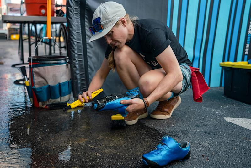 Brenna Wrye-Simpson cleaning bike shoes in the mechanic pits
