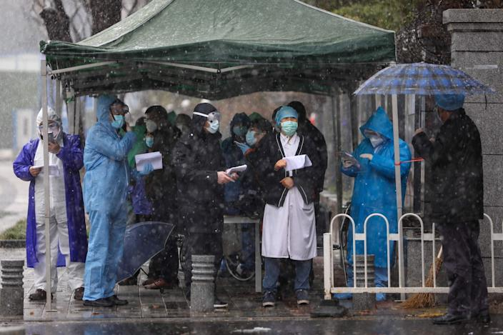 Medical staff and government workers wait for patients' arrival outside a tumor hospital which was just designated to take in critical COVID-19 patients in Wuhan in central China's Hubei province Saturday, Feb. 15, 2020.