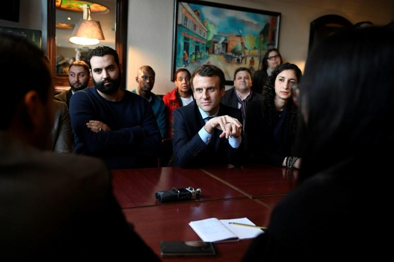 French presidential election candidate for the En Marche movement Emmanuel Macron (C) listens during a meeting organised in a bar in Les Mureaux on March 7, 2017