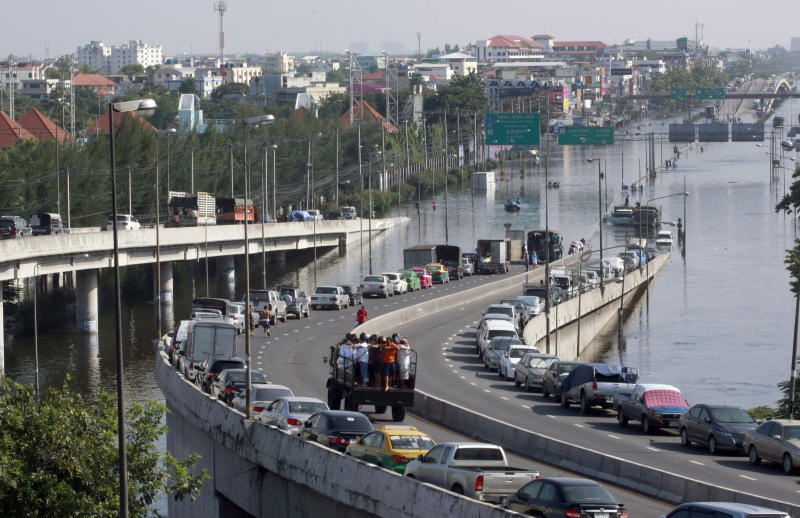FILE - In this Oct. 24, 2011 file photo, cars are parked on an overfly on a flooded street in Bangkok, Thailand. Sea level rise projections show Bangkok could be at risk of inundation in 100 years unless preventive measures are taken. But when the capital and its outskirts were affected in 2011 by the worst flooding in half-a century, the immediate trigger was water run-off from northern provinces, where dams failed to contain unusually heavy rains. (AP Photo/Apichart Weerawong, File)