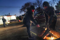 Volunteers Latrina Lawrence, left, and Breya Smith, roast marshmallows for motorists pulling through a drive-thru socially distanced Halloween celebration in the parking lot of The Winner's Circle Church in Mount Clemens, Mich., Saturday, Oct. 31, 2020. According to pastor Leon McDonald III, the event was intended to bring a sense of normalcy to its congregation amid coronavirus lockdowns and a sense of anxiety leading up to the election. (AP Photo/David Goldman)