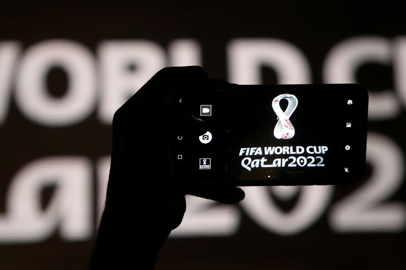 FILE PHOTO: A man takes a picture of the tournament's official logo for the 2022 Qatar World Cup as displayed on the wall of amphitheater, in Doha