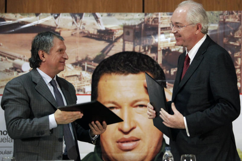 Venezuela's Oil Minister Rafael Ramirez, right, and Igor Sechin, chief executive of Russian energy company Rosneft, smile at each other after a signing ceremony in Caracas, Venezuela, Tuesday, Jan. 29, 2013.  Russian and Venezuelan officials signed five documents laying out plans for offshore natural gas and oil projects, the creation of a new joint company and the purchase of Russian-made oil drills. (AP Photo/Ariana Cubillos)