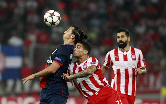Paris Germain's Zlatan Ibrahimovic, left, and Olympiakos' Carl Medjani, center, fight for the ball, during the soccer Champions League group C match between Olympiakos and Paris Saint Germain in Piraeus, Greece, Tuesday, Sept. 17, 2013. (AP Photo/Kostas Tsironis)