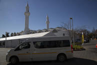 A minibus vehicle arrives at the Houghton Mosque, which is being used as a drive-thru COVID-19 vaccination centre in Johannesburg, Wednesday, July 28, 2021. Hitting its stride after a faltering start, South Africa's mass vaccination campaign gave jabs to 220,000 people a day last week and is accelerating toward the goal of 300,000 per day. With large deliveries of doses arriving and some vaccines being assembled here, South Africa appears on track to inoculate about 35 million of its 60 million people by the end of the year. (AP Photo/Denis Farrell)