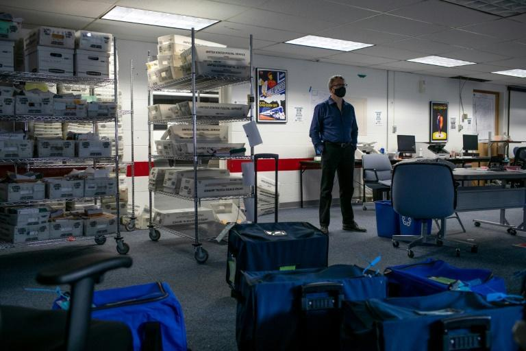 Lansing City Clerk Chris Swope stands amidst sealed containers of counted ballots following the end of vote counting Lansing, Michigan