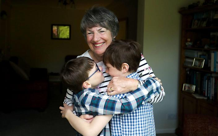 Sue Rickett hugs her grandchildren Ben (right) and Isaac (left) for the first time in over a year - Martin Rickett/PA