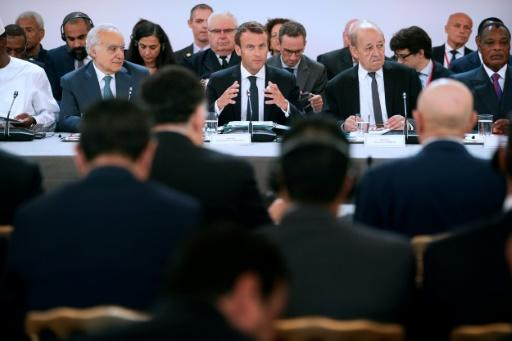 French President Emmanuel Macron, flanked by Foreign Minister Jean-Yves Le Drian (2R) and UN Special Envoy for Libya, Lebanese Ghassan Salame (L) speaks during an International conference on Libya at the Elysee Palace in Paris, on May 29, 2018