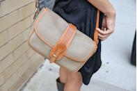 <p>In 1981, Dooney & Bourke branched out of making belts and suspenders and moved onto handbags, and just a couple years later everyone was wearing the brand's leather purses, like this beige and tan cross-body. </p>