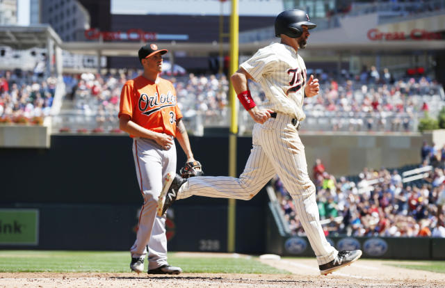 Baltimore Orioles pitcher Kevin Gausman, left, looks on as Minnesota Twins' Jake Cave scores on a wild pitch in the fifth inning of a baseball game Saturday, July 7, 2018, in Minneapolis. (AP Photo/Jim Mone)