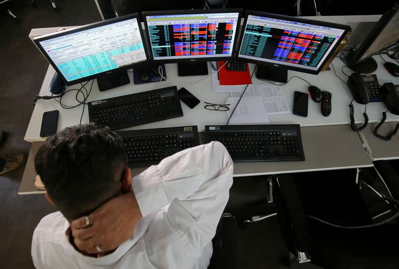 FILE PHOTO: A broker reacts while trading at his computer terminal at a stock brokerage firm in Mumbai