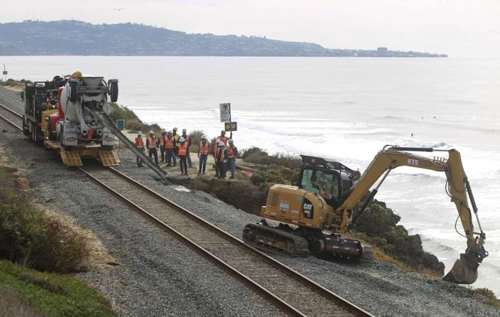 Workers repair the site of a bluff collapse next to the railroad tracks, which was caused by a washout from the recent rains, in Del Mar on Saturday, November 30, 2019 in Del Mar, California.