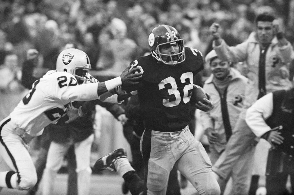 """FILE - In this Dec. 23, 1972, file photo, Pittsburgh Steelers' Franco Harris (32) eludes a tackle by Oakland Raiders' Jimmy Warren as he runs 42-yards for a touchdown after catching a deflected pass during an AFC Divisional NFL football playoff game in Pittsburgh. Harris' scoop of a deflected pass and subsequent run for the winning touchdown _ forever known as the """"Immaculate Reception"""" _ has been voted the greatest play in NFL history. A nationwide panel of 68 media members chose the Immaculate Reception as the top play with 3,270 points and 39 first-place votes. (AP Photo/Harry Cabluck, File)"""