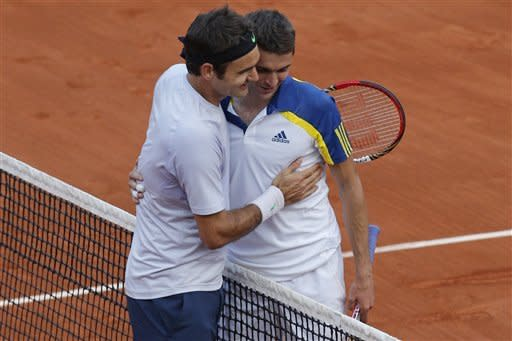 Switzerland's Roger Federer, left, hugs France's Gilles Simon, after defeating him in five sets 6-1, 4-6, 2-6, 6-2, 6-3, in their fourth round match at the French Open tennis tournament, at Roland Garros stadium in Paris, Sunday June 2, 2013. (AP Photo/Christophe Ena)