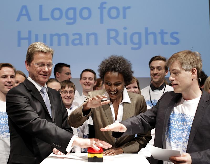 German Foreign Minister Guido Westerwelle, the jury member and Model Waris Dirie from Somalia and the German comedian Michael Mittermaier, from left, press the start button for the humanrightslogo.net website in Berlin, Germany, Tuesday, May 3, 2011. Germany and several other countries think it's time to create a universal human rights logo. On Tuesday, the Foreign Ministry in Berlin launched an international campaign to find a symbol that could be used by activists, politicians and others around the world. (AP Photo/Michael Sohn)