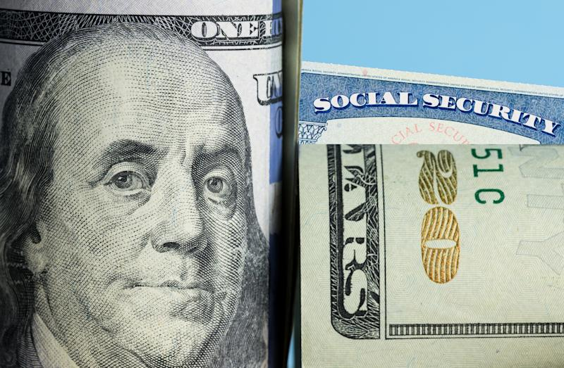 A rolled-up hundred dollar bill and twenty dollar bill partially covering a Social Security card.