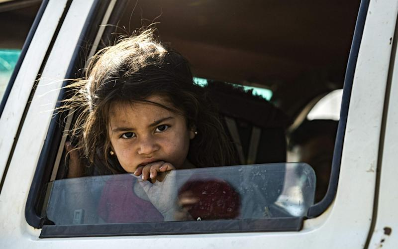 A young Syrian girl fleeing with her family from northern Syria - AFP