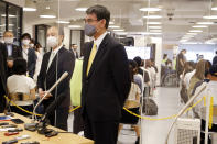 Covid 19 Vaccine Minister Taro Kono, center, and Masayoshi Son, chief executive of technology company SoftBank Group Corp., left, speak to media after visiting an inoculation site set up by Japanese technology company SoftBank Group Corp. at a WeWork office Tuesday, June 15, 2021, in Tokyo. Japanese companies have joined the effort to speed up the country's lagging coronavirus vaccine rollout before the Tokyo Olympics begin next month. (AP Photo/Yuri Kageyama)