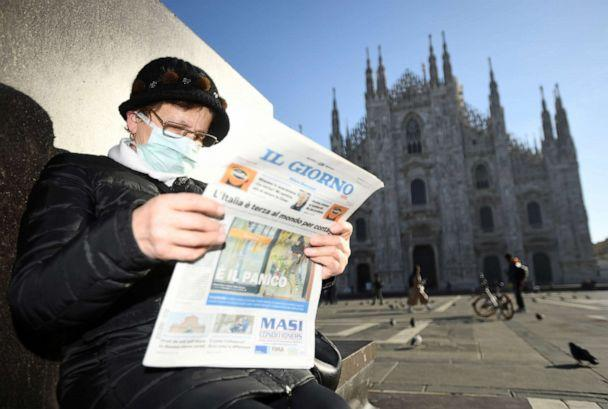 PHOTO: A woman reads a newspaper outside Duomo cathedral, closed by authorities due to a coronavirus outbreak, in Milan, Italy, Feb. 24, 2020. (Flavio Lo Scalzo/Reuters, FILE)