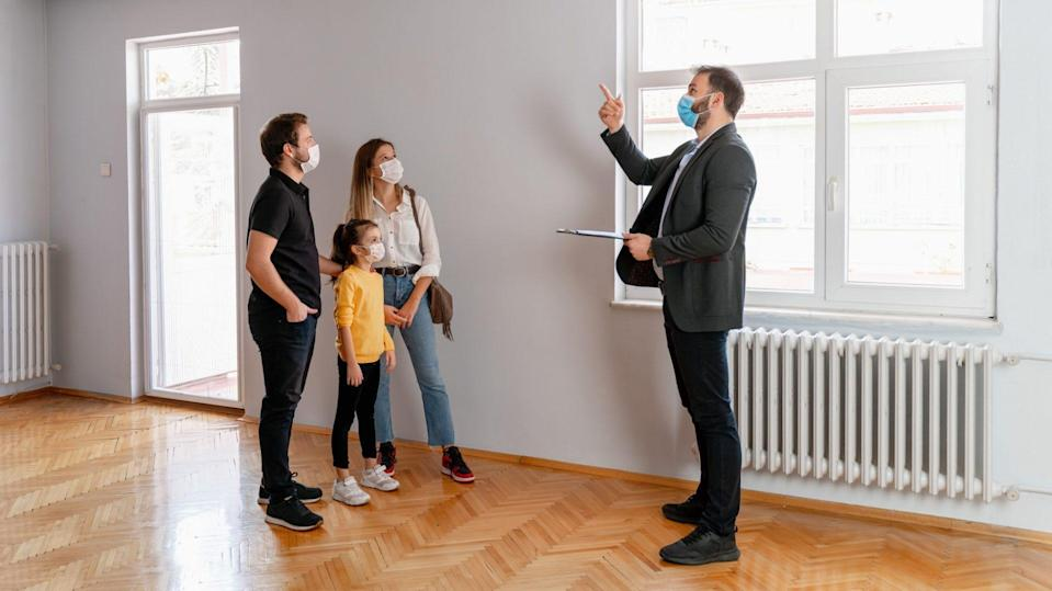Confident male real estate agent gestures toward a beautiful view out the window of a new home.
