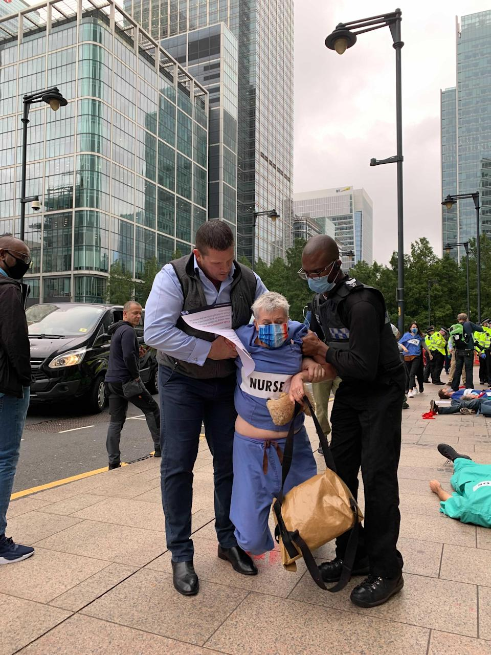 This woman dressed in nursing scrubs was led away by security (The Independent)