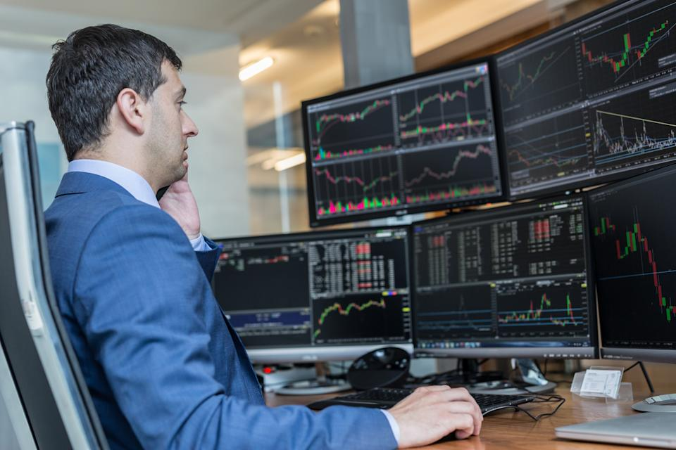 Male stock broker trading online watching charts and data analyses on multiple computer screens. (Source: Getty Creative)