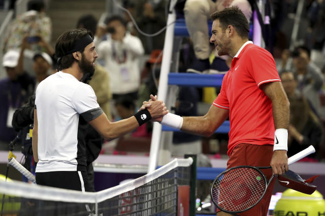 Nikoloz Basilashvili of Georgia, left, and Juan Martin del Potro of Argentina meet at the net after the men's singles final in the China Open at the National Tennis Center in Beijing, Sunday, Oct. 7, 2018. (AP Photo/Mark Schiefelbein)