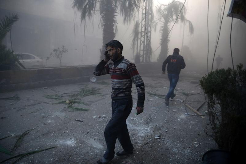 A wounded man walks out of a dust cloud following reported airstrikes in the town of Hamouria in the eastern Ghouta region, a rebel stronghold east of the Syrian capital Damascus, on December 9, 2015 (AFP Photo/Sameer Al-Doumy)