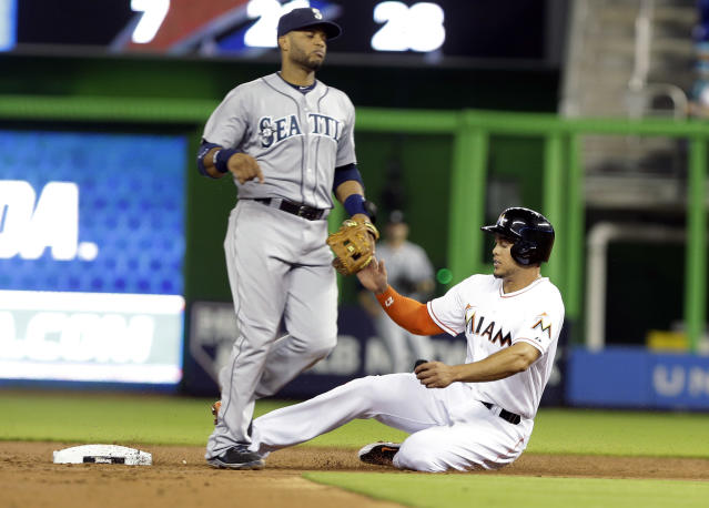 Miami Marlins' Giancarlo Stanton, right, is safe at second next to Settle Mariners' second baseman Robinson Canoon a wild pitch by Mariners starting pitcher Chris Young during the first inning of an interleague baseball game on Friday, April 18, 2014, in Miami. (AP Photo/Lynne Sladky)