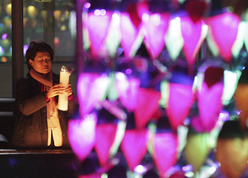 A Buddhist woman holding a candle light prays ahead of the new year at Chogye Buddhist temple in Seoul, South Korea, Tuesday, Dec. 31, 2013. (AP Photo/Ahn Young-joon)