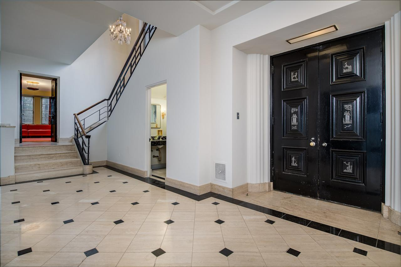 The entry hall leads to the dramatic stone staircase, which features a custom aluminum railing, and the library. The couple initially wanted a smaller home, but the size expanded during the design process.