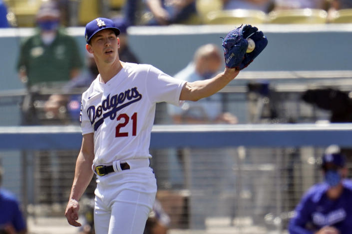 Los Angeles Dodgers starting pitcher Walker Buehler gets the ball back from the infield after recording an out during the fourth inning of a baseball game against the Washington Nationals, Friday, April 9, 2021, in Los Angeles. (AP Photo/Marcio Jose Sanchez)