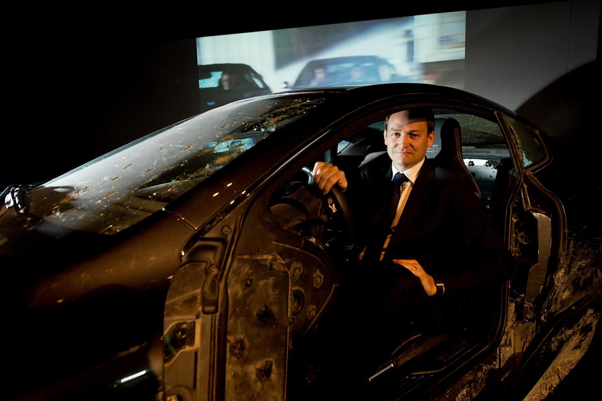 Stunt driver Ben Collins sits in one of the Aston Martin DBS cars that he used in the James Bond film