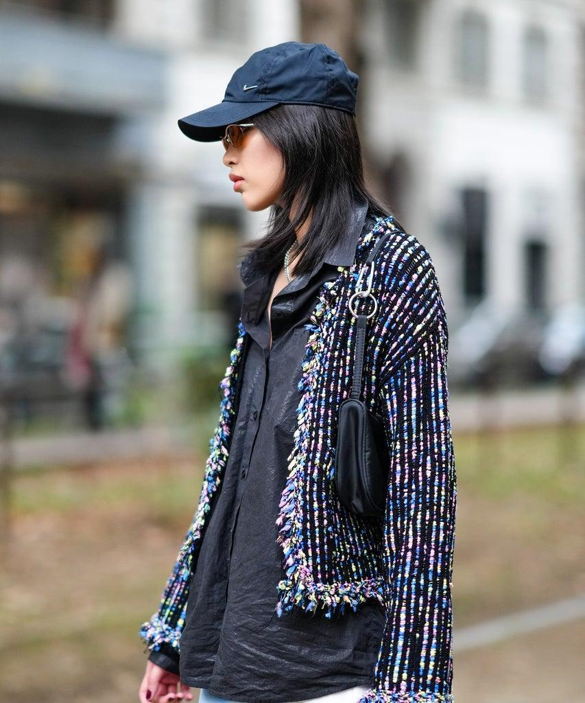 MILAN, ITALY – SEPTEMBER 25: A guest wears a black cap from Nike, sunglasses, earrings, a silver chain necklace with a cigarette butt pendant, a black shiny shirt, a black with pale pink / blue / green braided wool stripes cardigan pullover, white with blue / purple print pattern skinny flared pants, outside the Dolce & Gabbana fashion show during the Milan Fashion Week – Spring / Summer 2022 on September 25, 2021 in Milan, Italy. (Photo by Edward Berthelot/Getty Images)
